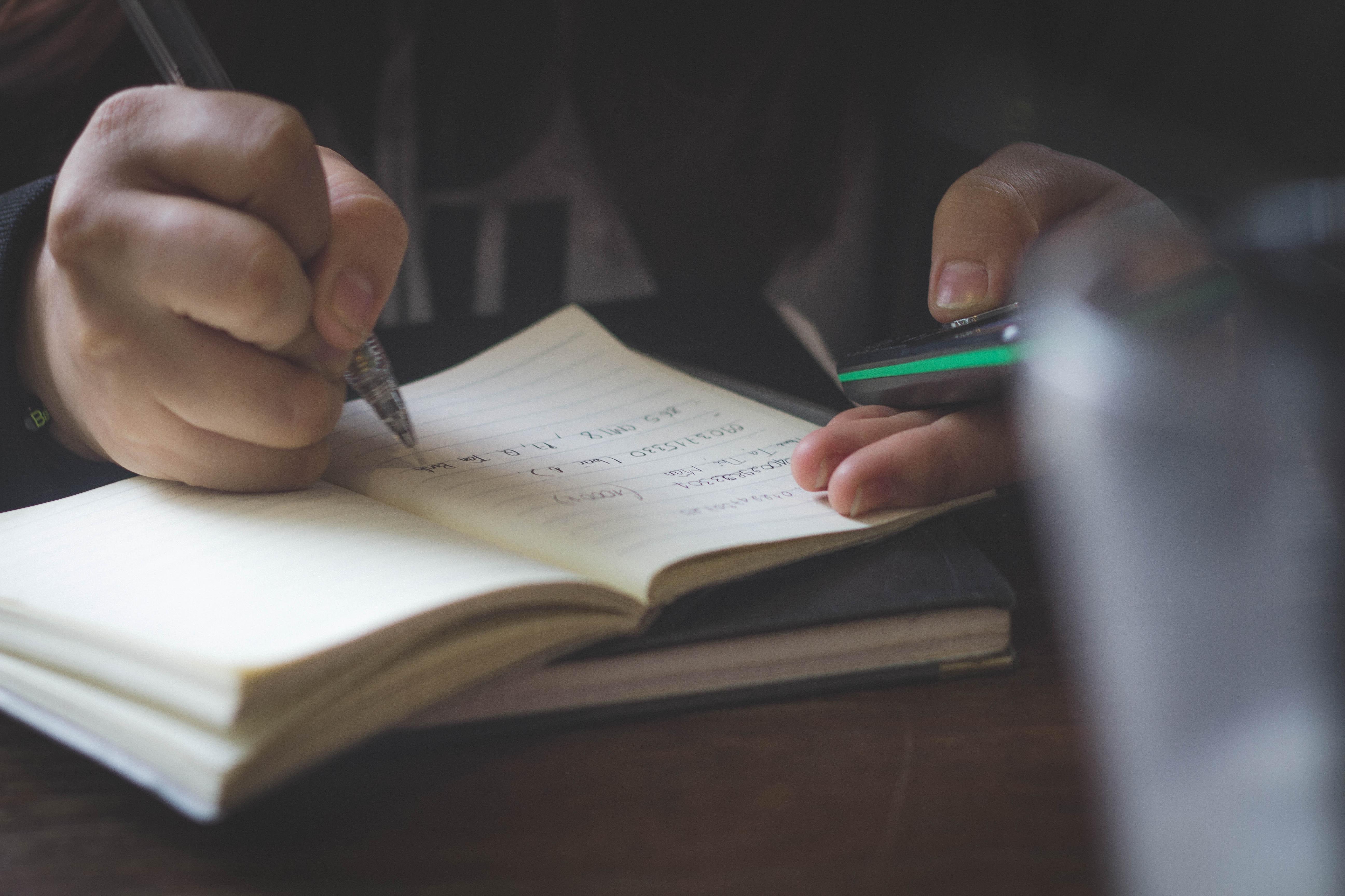 une personne qui ecrit une note sur un livre